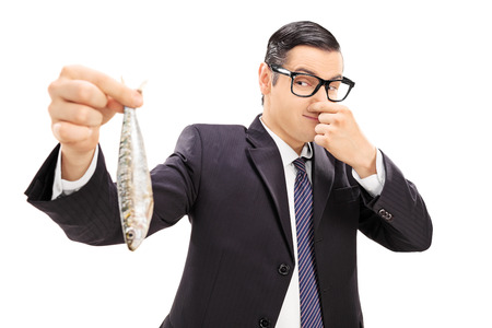 Young businessman holding a stinky fish isolated on white background photo