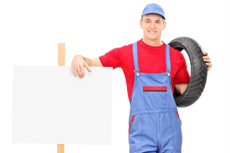 Male mechanic standing next to a blank sign isolated on white background photo