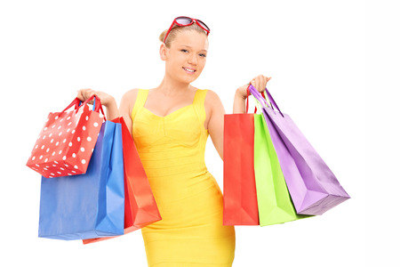 Woman holding a bunch of shopping bags isolated on white background photo