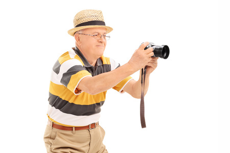 Mature man taking a picture with a camera isolated on white background photo
