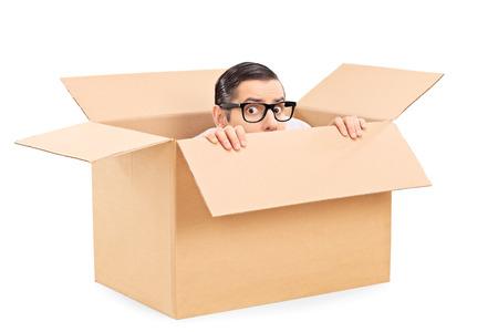 hombre asustado: Hombre asustado que oculta en una caja de cart�n aisladas sobre fondo blanco Foto de archivo
