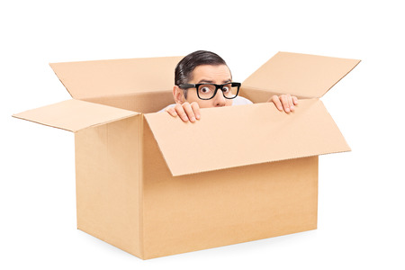hide: Scared man hiding in a carton box isolated on white background