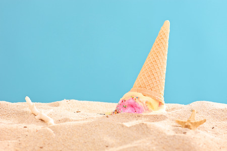 Studio shot of an ice cream splashed on sand on blue background