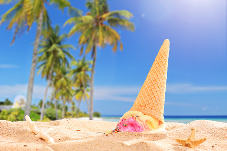 crushed ice: Ice cream splashed in the sand on a beach on a sunny day with the focus on the ice cream  Stock Photo