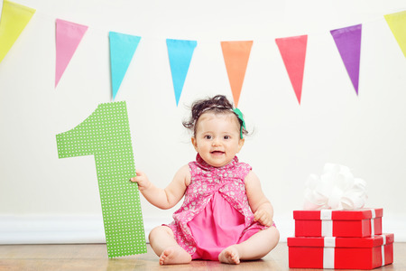 Baby girl sitting by a bunch of presents on a birthday party