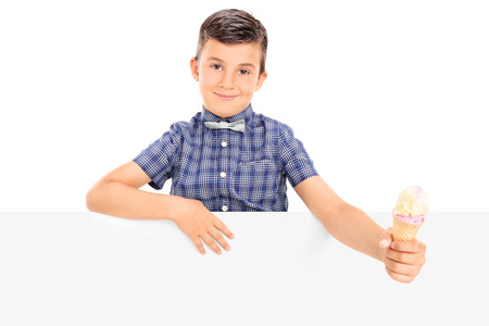 Cute little boy holding an ice cream behind a panel isolated on white background photo