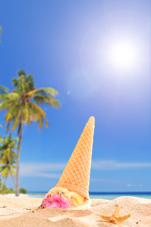 abolished: An ice cream melting in the sand on a tropical beach on sunny day