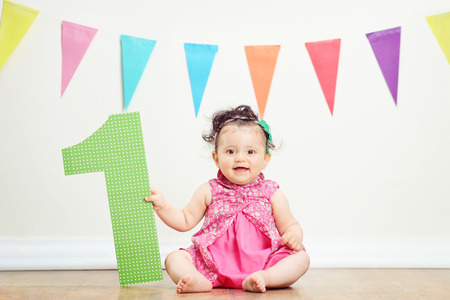 Happy baby girl on her first birthday party seated on the floor Stock Photo