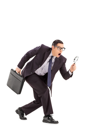 baffled: Sneaky businessman looking through a magnifying glass isolated on white background Stock Photo