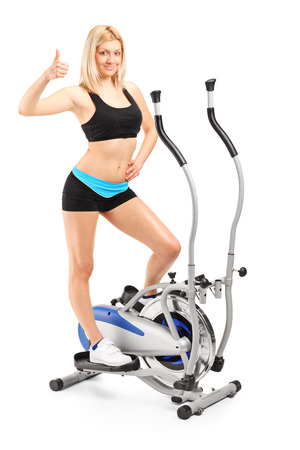 Full length portrait of a woman giving a thumb up on a cross trainer machine isolated on white background photo