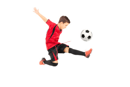 uniforme de futbol: Futbolista menor patear una pelota aislados sobre fondo blanco