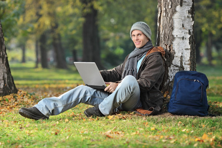 Relaxed young man working on laptop seated by a tree in park photo