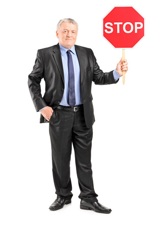 Full length portrait of a mature businessman holding a stop sign isolated on white background photo