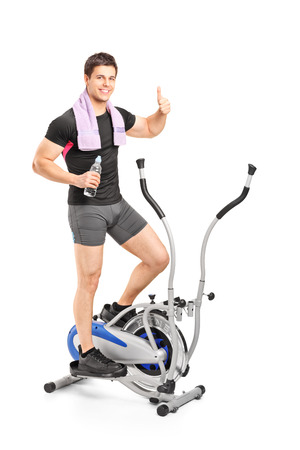 Full length portrait of a young guy exercising on a cross trainer machine isolated on white background photo