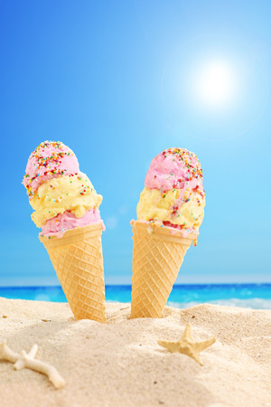 Two ice cream cones stuck in the sand on a sunny beach  photo