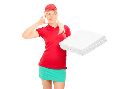 Delivery girl making a call sign and holding pizza boxes isolated on white background photo