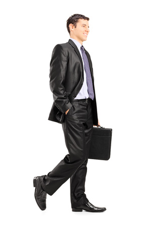 business briefcase: Happy business man holding a briefcase and walking isolated on white background Stock Photo