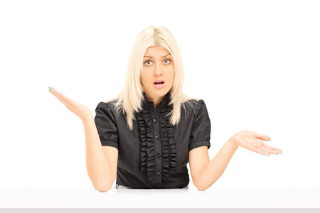 confused woman: Confused woman gesturing with hands seated at a table isolated on white background