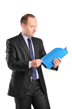 Vertical shot of a businessman reading a document isolated on white background photo