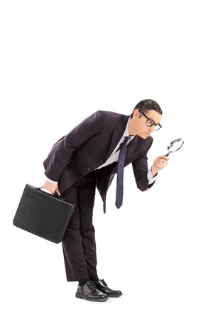 inspecting: Displeased businessman looking through a magnifying glass isolated on white background