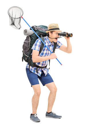 butterfly net: Full length portrait of a guy with butterfly net looking through binoculars isolated on white background