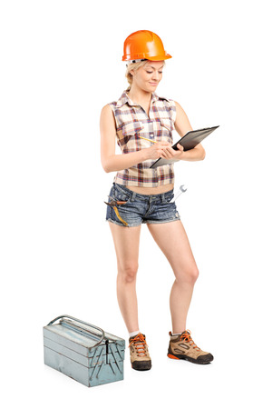 Full length portrait of a female mechanic writing on a clipboard isolated on white background photo