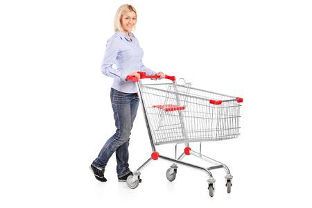 Retrato cheio do comprimento de uma mulher empurrando um carrinho de compras isolado no fundo branco