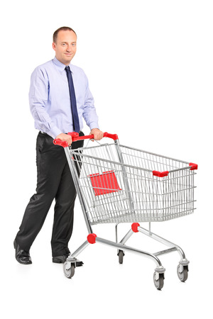 Full length portrait of a young man pushing a shopping cart isolated on white background photo