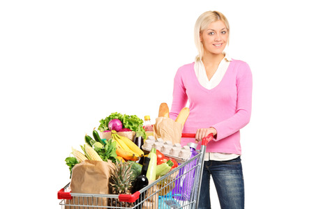 grocery shopping cart: Woman pushing a shopping cart full of groceries isolated on white background Stock Photo