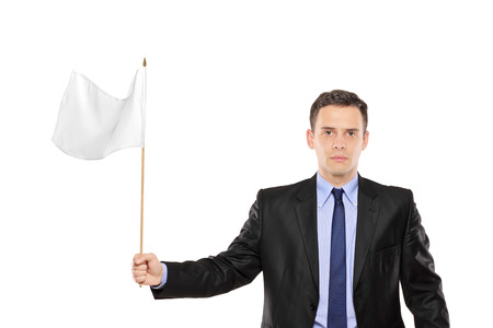 surrender: Young businessman waving a white flag isolated on white background