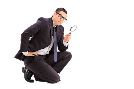evaluating: Male inspector looking through a magnifying glass isolated on white background Stock Photo