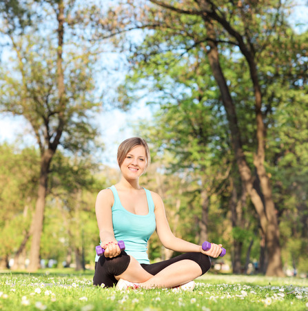 Young girl exercising with dumbbells in park seated on grass photo