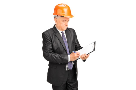 taking notes: Mature construction worker taking notes on a clipboard isolated on white background