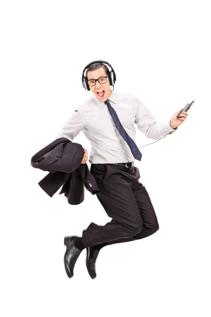 Ecstatic businessman listening to music on his cell phone isolated on white background photo