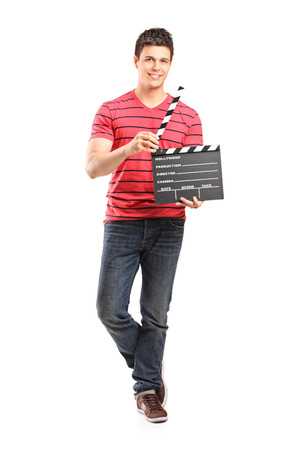 filmmaker: Full length portrait of a young filmmaker holding a movie-clapper isolated on white background Stock Photo