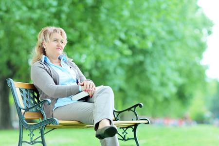 mujer pensativa: Mujer pensativa maduro sentado solo en el parque