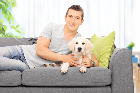 man dog: Happy young man lying on a couch with a Labrador puppy at home