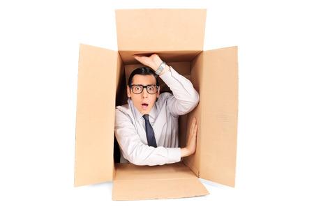 confundido: Hombre de negocios joven atrapado en una caja aislada sobre fondo blanco