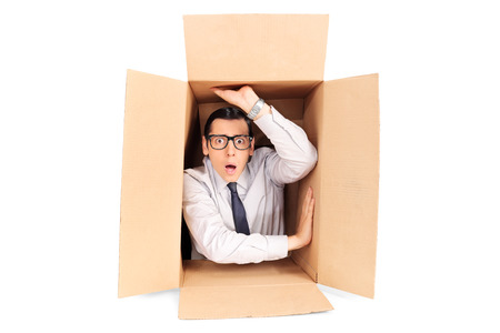 Young businessman trapped in a box isolated on white background Фото со стока