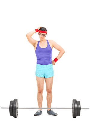 insecure: Full length portrait of a doubtful male athlete standing behind a barbell isolated on white background