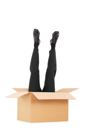Vertical shot of male legs sticking out of a box isolated on white background photo
