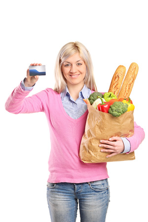 woman holding bag: Woman holding bag with groceries and a blank card isolated on white background