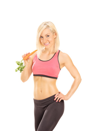 mujer deportista: Mujer atractiva en ropa deportiva que come una zanahoria aisladas sobre fondo blanco