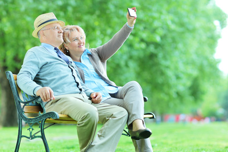 Elderly couple taking a selfie in the park seated on a bench photo
