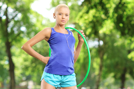 Female athlete on a mat holding a hula hoop in a park photo