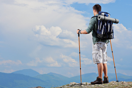 trekker: Male hiker standing on a mountain top and holding hiking poles
