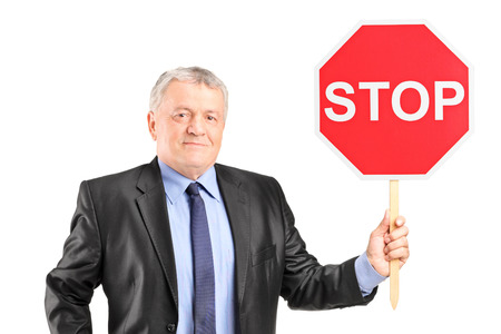 Mature businessman holding a stop sign isolated on white background photo