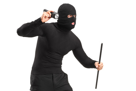 scammer: Robber with mask holding a flashlight and piece of pipe isolated on white background Stock Photo