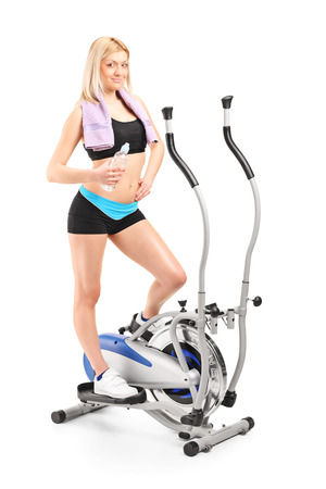 Full length portrait of a woman holding a water bottle on a cross trainer machine isolated on white background photo
