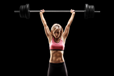 weightlifter: Muscular woman lifting a heavy barbell on black background Stock Photo